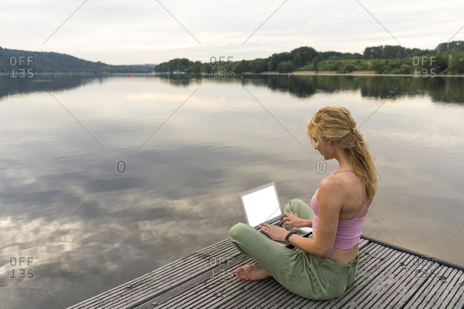 Young woman using laptop on a jetty at a lake