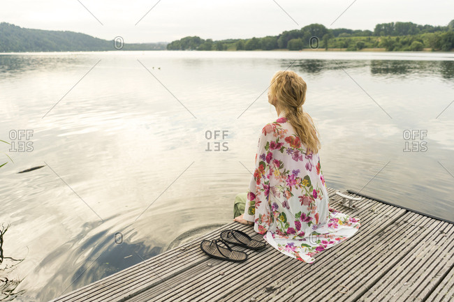 Young woman sitting on a jetty at a lake