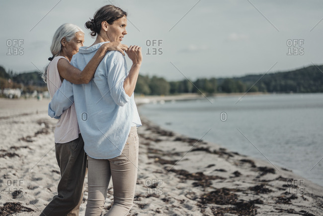 Mother and daughter spending a day at the sea- embracing on the beach