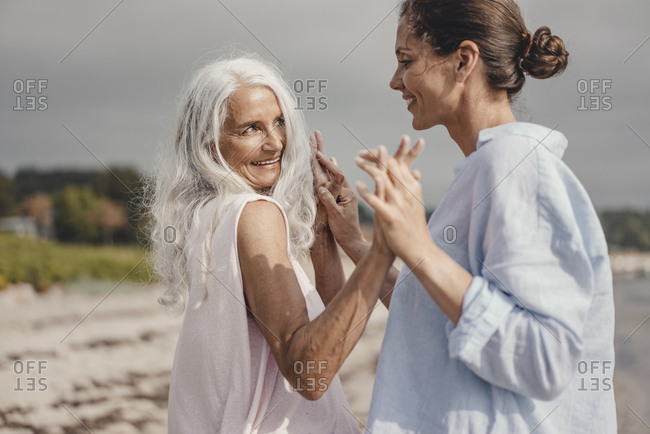 Mother and daughter spending a day at the sea- dancing on the beach
