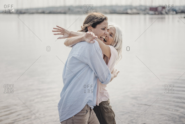 Mother and daughter spending a day at the sea- laughing and embracing