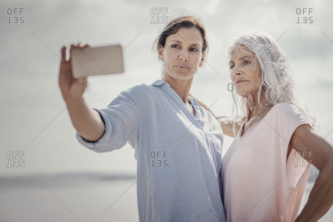 Mother and daughter spending a day at the sea- taking smartphone selfies