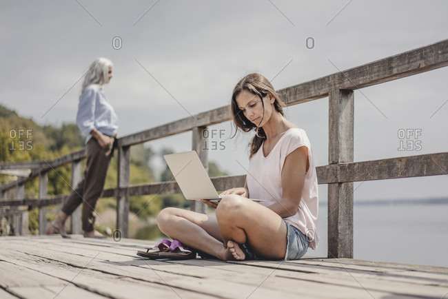 Woman sitting on wood bridge- using laptop- mother standing in background