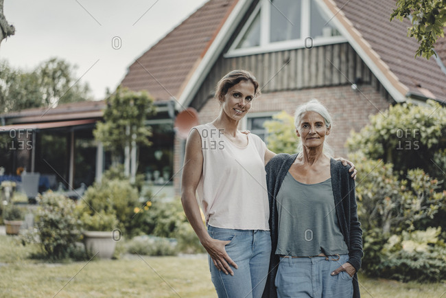 Mother and daughter standing in garden- inf ront of their house