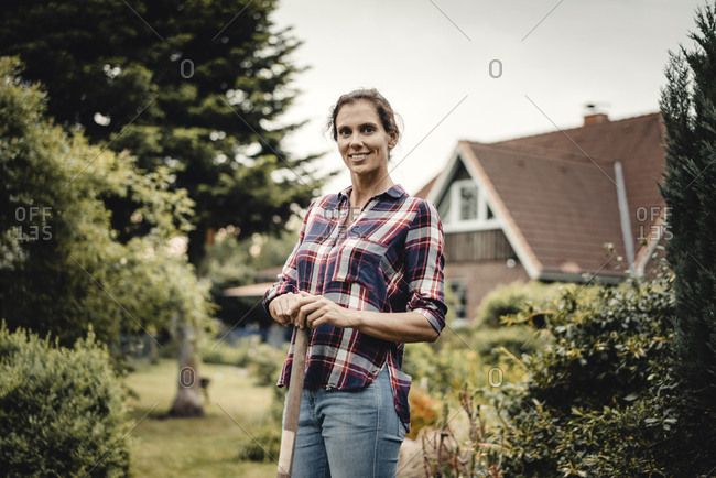 Proud home owner standing in her garden with a spade