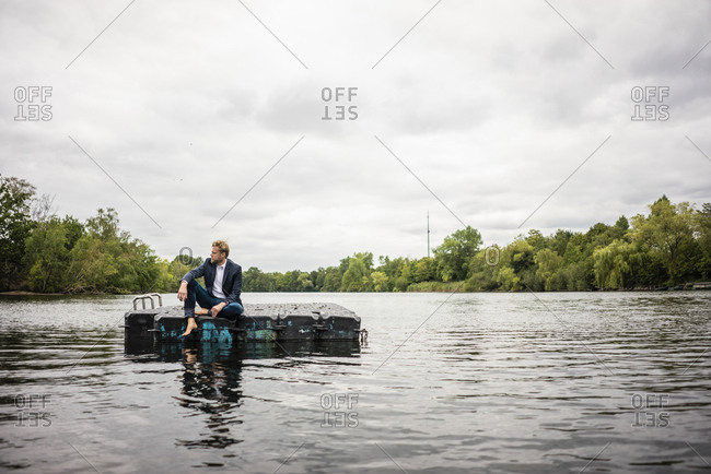 Businessman sitting on a float a lake