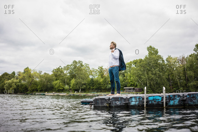 Businessman standing on a float a lake looking out
