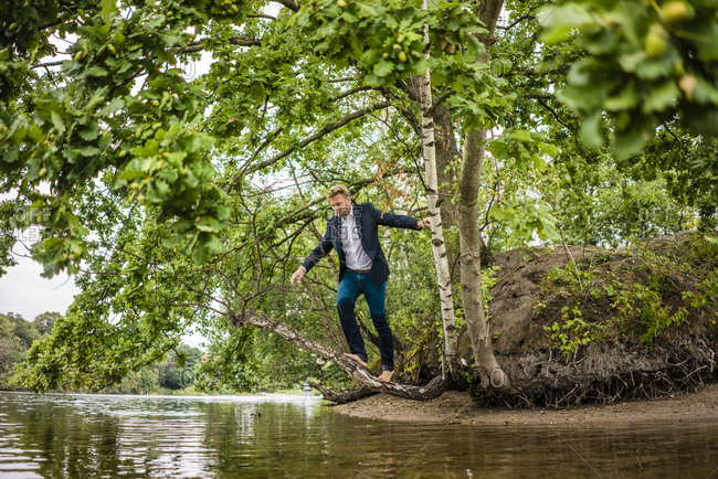 Businessman balancing on tree trunk over a lake