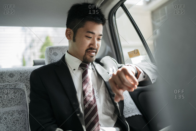 Young businessman in a taxi checking the time