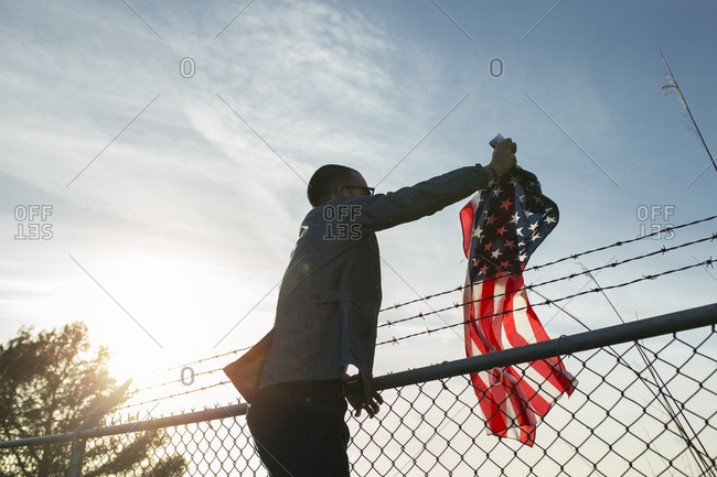 Young man removing US-American flag from brabed wire fence