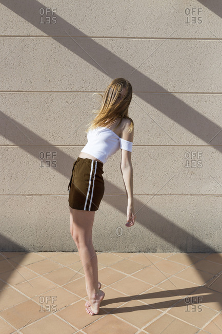 Young fashionable woman standing on tippy toes- face obscured