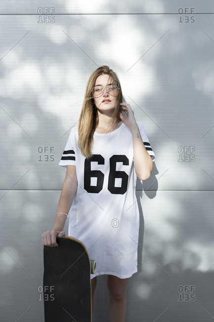 Young woman wearing t-shirt with number 66- holding skateboard