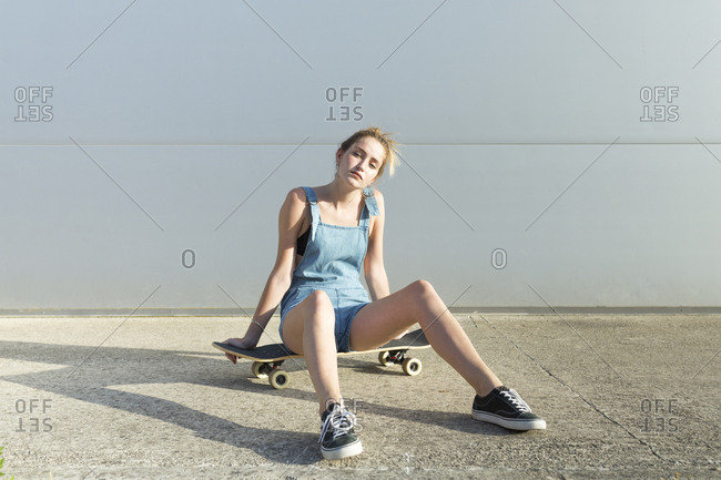 Cool young woman sitting on skateboard