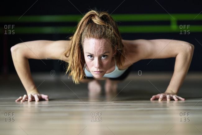 Sporty young woman doing push-ups in exercise room
