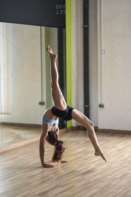 Sporty young woman doing a handstand in exercise room