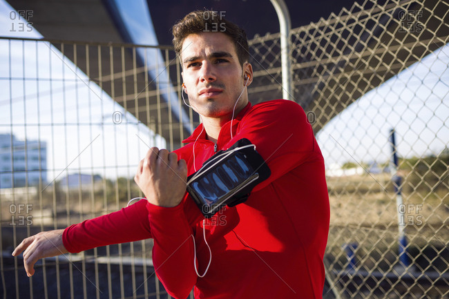 Jogger with smartphone in arm pocket- stretching his arm