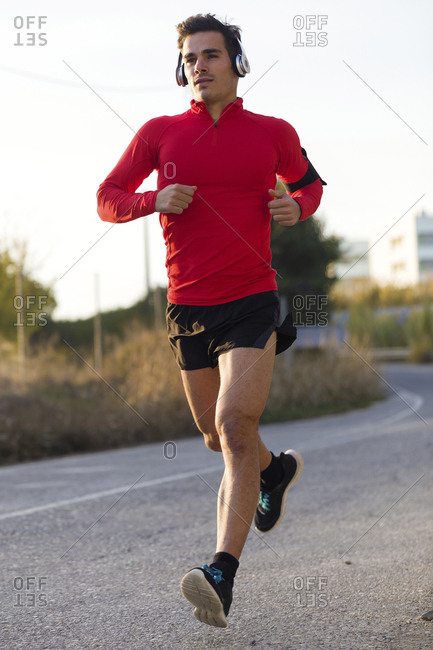 Jogger with smartphone in arm pocket and headphones