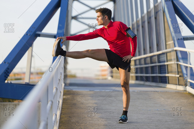 Jogger with smartphone in arm pocket stretching his leg