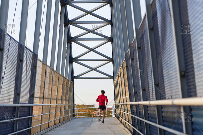 Rear view of a jogger with smartphone in arm pocket running on a bridge