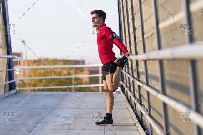 Jogger with smartphone in arm pocket- stretching his leg on a bridge railing