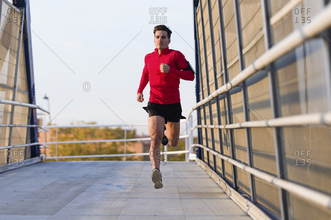 Jogger with smartphone in arm pocket running on a bridge