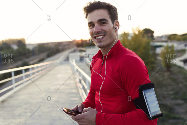 Jogger with smartphone in arm pocket- holding smartphone and looking at camera
