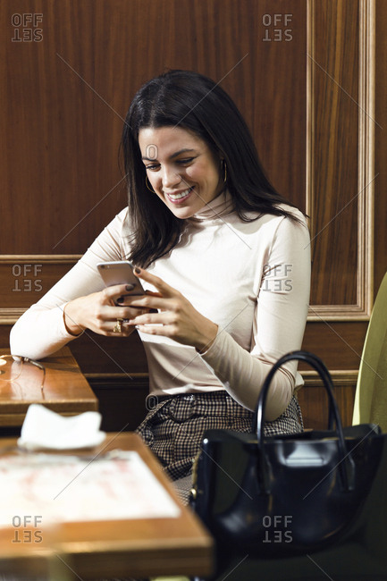 Smiling businesswoman using cell phone in a restaurant