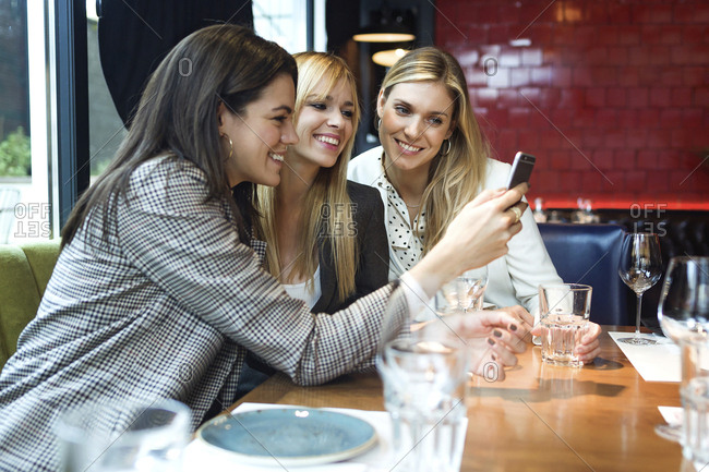 Three happy businesswomen in a restaurant looking at smartphone together