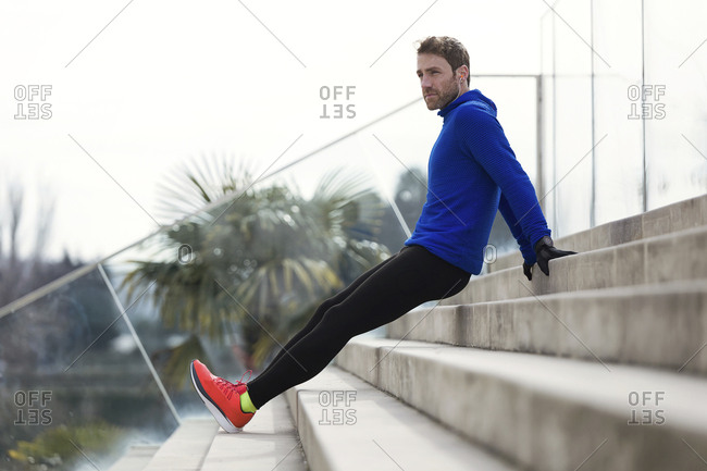 Jogger stretching his legs on steps