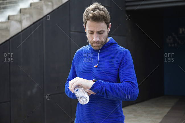 Portrait of jogger with water bottle- checking workout progress on his smart watch