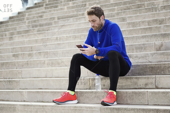 Jogger sitting on steps and using smartphone