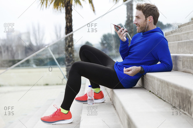 Jogger sitting on steps talking on mobile phone with hands free