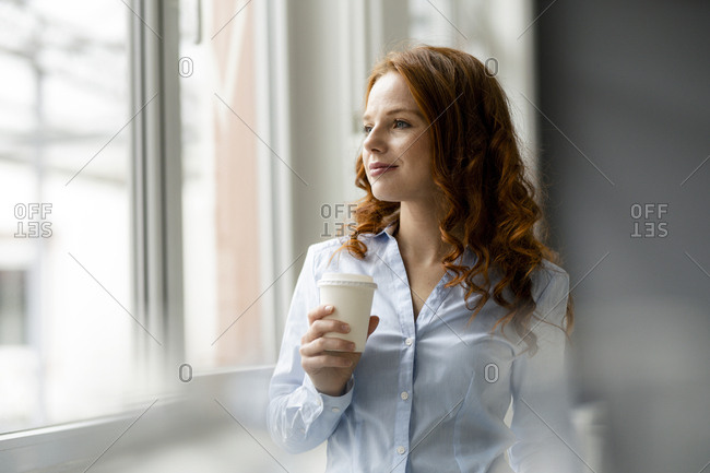 Portrait of redheaded businesswoman with coffee to go looking out of window