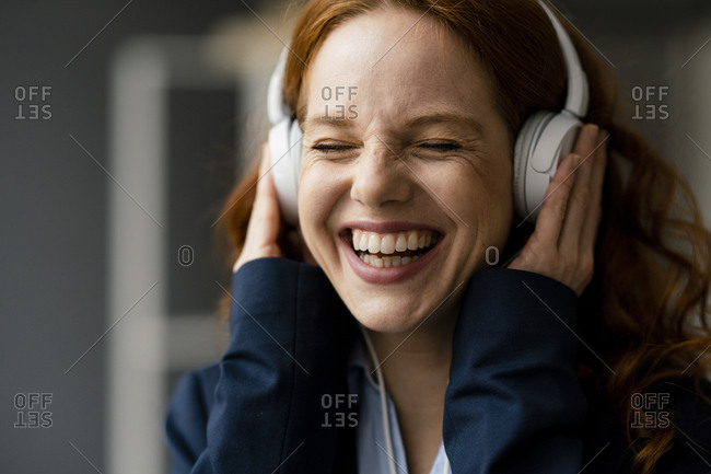 Portrait of laughing redheaded businesswoman listening music with white headphones