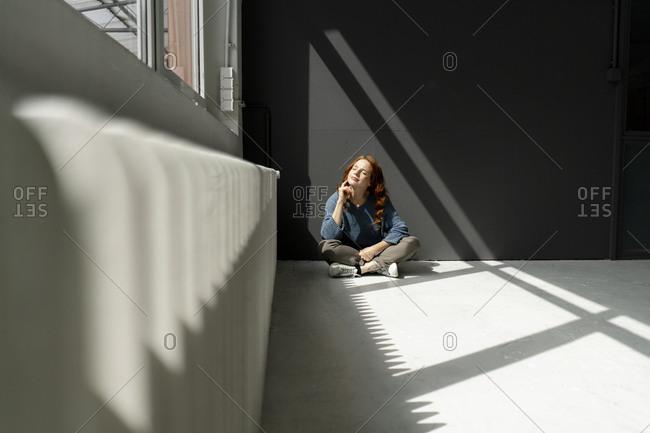 Redheaded woman sitting on floor of a loft enjoying sunlight