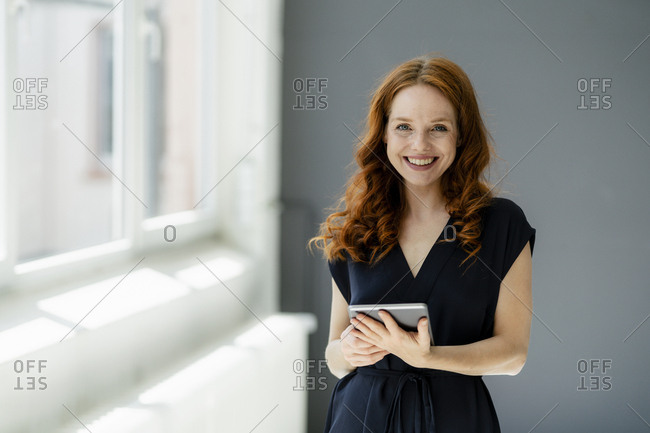 Portrait of content redheaded businesswoman with digital tablet in a loft