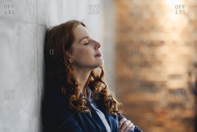 Redheaded businesswoman having a break leaning against a wall in office