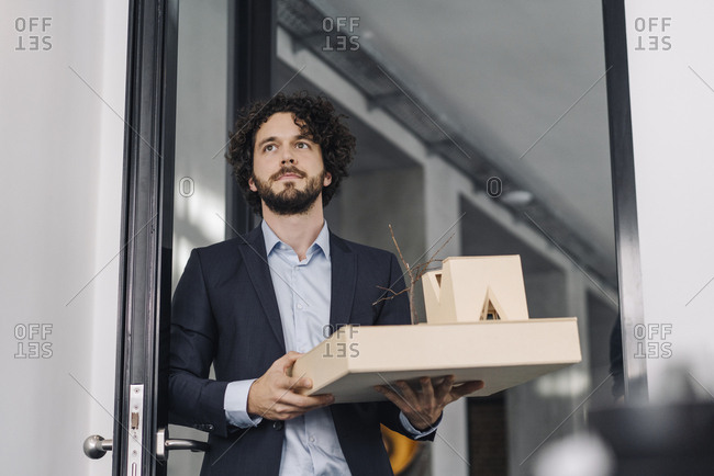 Architect in office holding architectural model