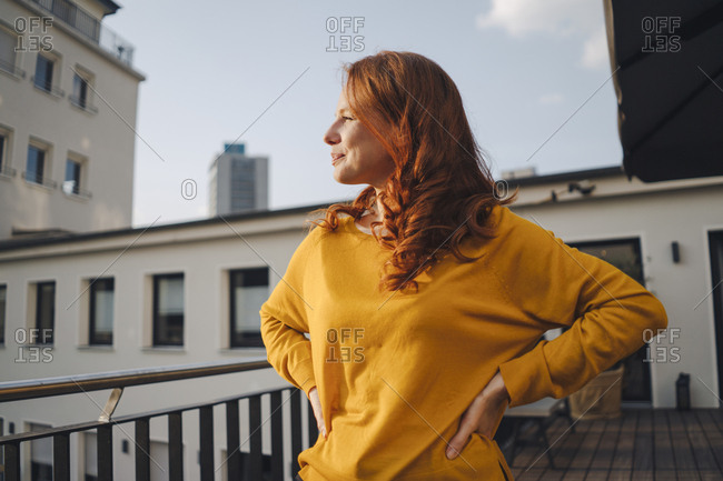Redheaded woman standing on roof terrace
