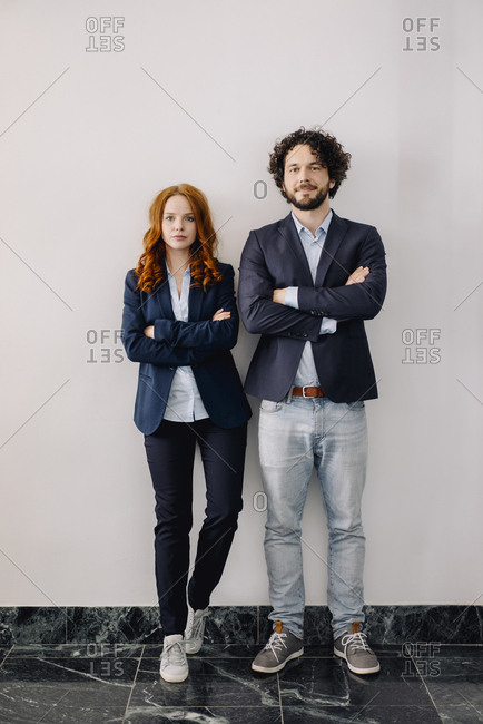 Portrait of confident businessman and businesswoman standing side by side