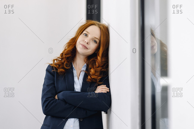 Portrait of redheaded businesswoman leaning against a wall