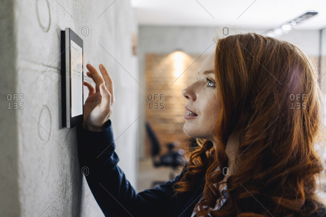 Businesswoman using device at a wall