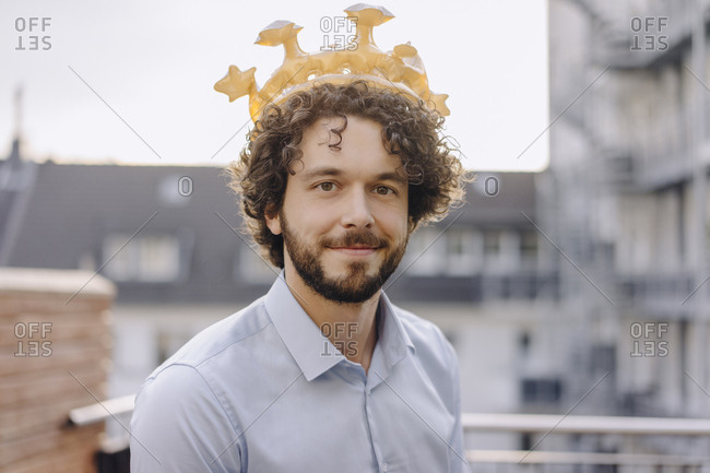 Portrait of confident businessman on roof terrace wearing a crown