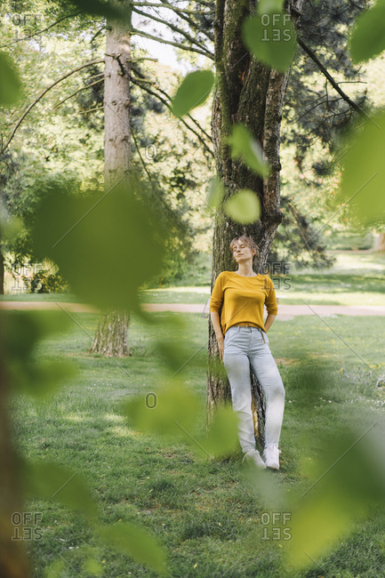 Young woman leaning against a tree in park