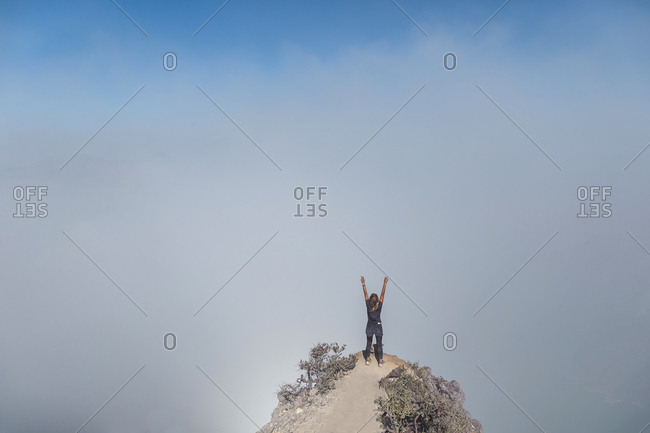 Woman with raised arms on view point- Ijen volcano- Java- Indonesia