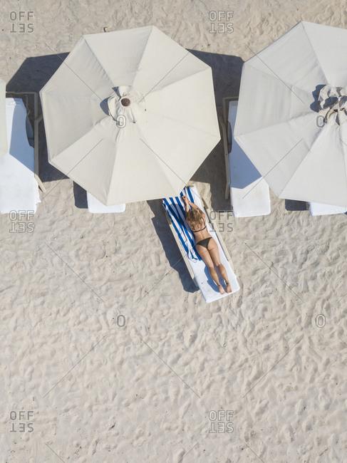 Woman lying on sun lounger at the beach- Gili Air- Gili Islands- Indonesia