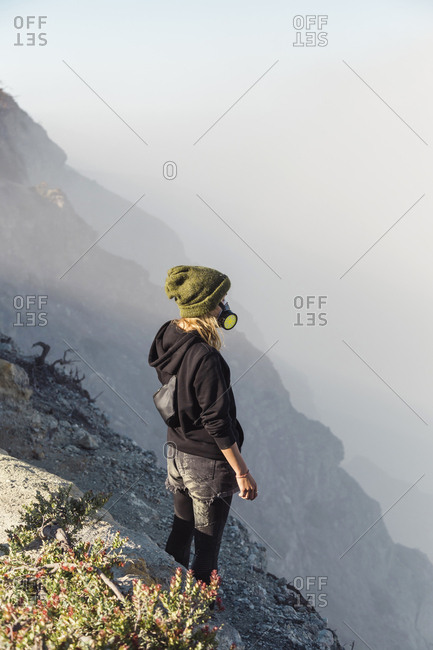 Young woman with respirator mask standing at the edge of volcano Ijen- Java- Indonesia