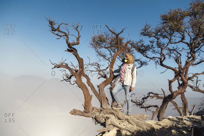 Woman with respirator mask on a tree at volcano Ijen- Java- Indonesia