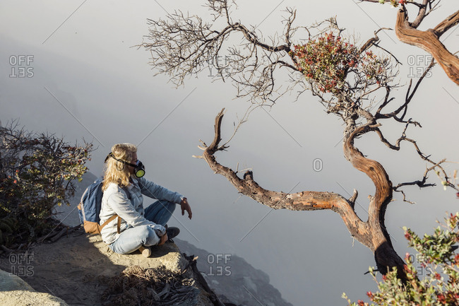 Woman with respirator mask sitting at volcano Ijen- Java- Indonesia