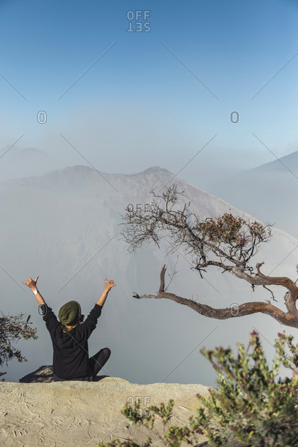 Woman with respirator mask sitting at volcano Ijen and  raising her arms- Java- Indonesia